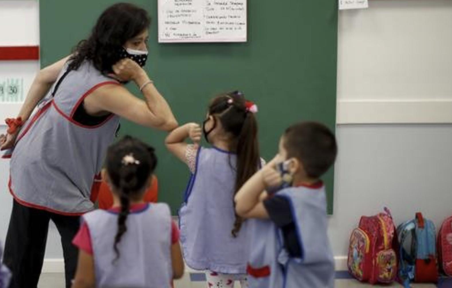 Una maestra, en Buenos Aires, enseña a sus alumnos de cinco años a saludar con un codazo durante el regreso a las aulas en medio de la pandemia. Foto Ap / archivo